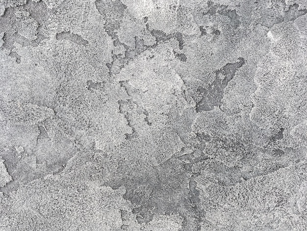 Old gray wall covered with uneven plaster. texture of vintage shabby silver stone surface, closeup.