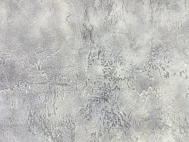 Old gray wall covered with uneven plaster, texture of vintage shabby silver stone surface