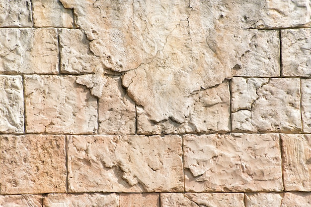 Old gray wall of rectangular stone blocks with remnants of plaster. abstract background