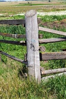家畜の移動を制限する農民の畑にある古い灰色の木製の柵