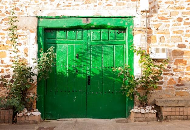 貧しいスペインの家の古い緑のドア