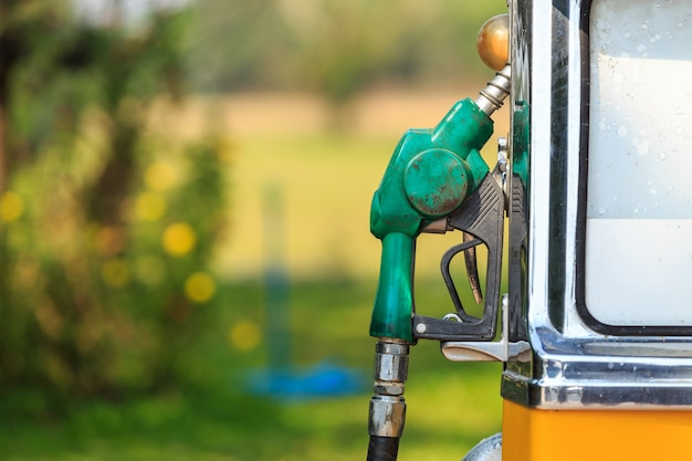 Old of green fuel nozzle in gas station on green blur background