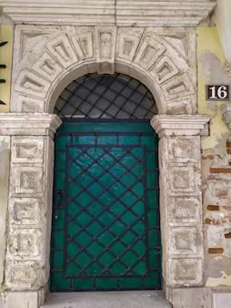 Старая зеленая металлическая дверь с решеткой в старинной круглой арке