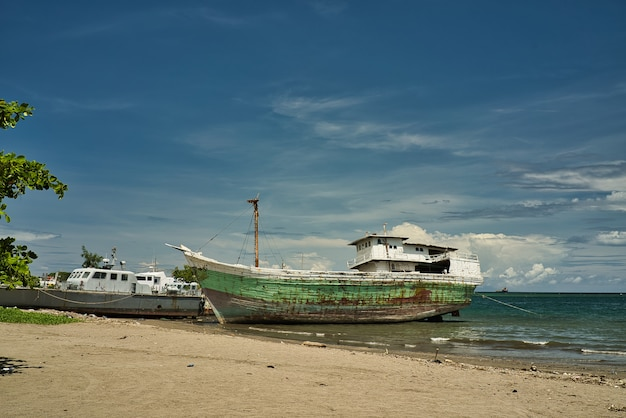 Old green painted wooden boat on the beach sand.