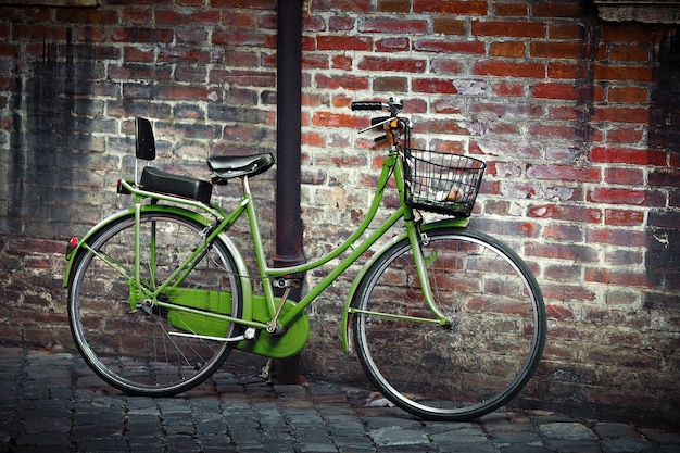 Old green retro bycicle with basket against grunge wall in ravenna, italy