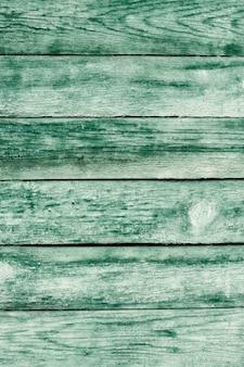 ひびの入ったカラーペイントと古い緑のみすぼらしい木製の板