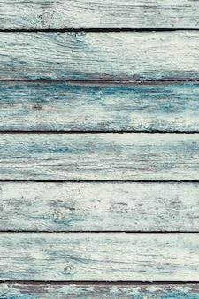 ひびの入った色の塗料で古い緑のぼろぼろの木製の板