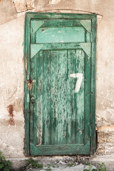 Old green wooden doors with the number seven, a dilapidated wall.