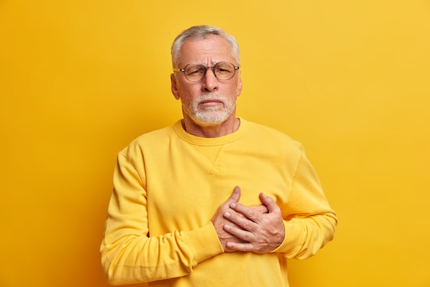 Old grey haired man suffers chest pain has heart attack needs painkillers dressed in casual clothes isolated over vivid yellow wall