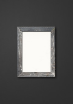 Old grey rustic wooden picture frame hanging on a black wall. blank  template