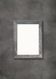 Old grey rustic wooden picture frame hanging on a dark concrete wall. blank mockup template