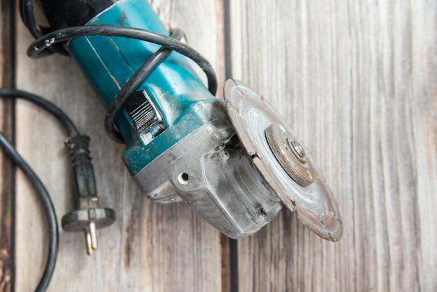 木製の背景の上に敷設古いグラインダー。電動工具の平置きビュー