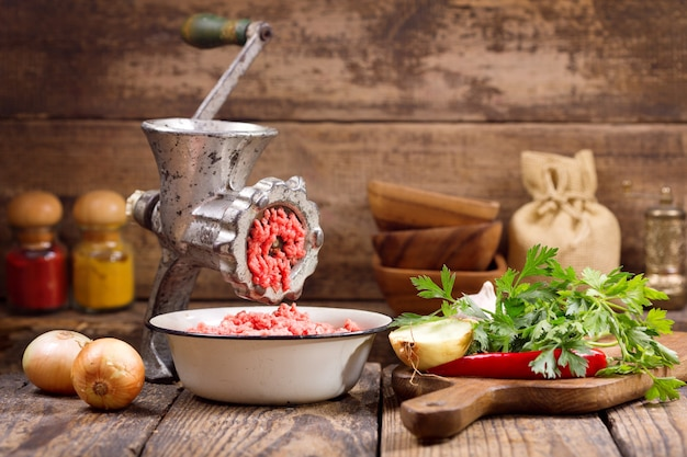 Старая мясорубка с фаршем и овощами на деревянном столе
