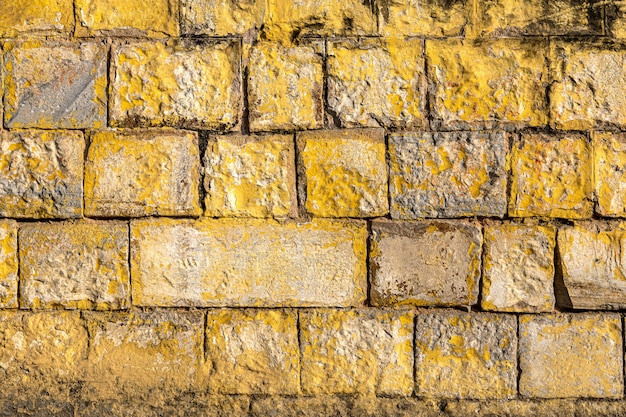 Old grunge brick wall painted yellow color of background and texture.