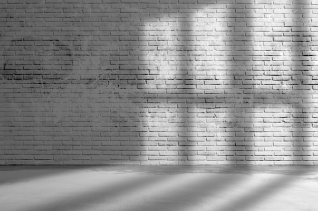 Old grunge rough dark gray brick wall wall with window shadow and concrete floor texture background