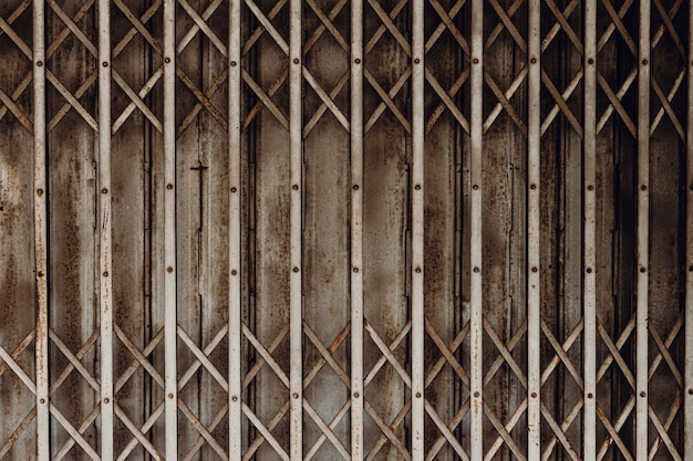 Old grunge rusty shutter folding door for shop closed or business down concept, texture pattern or steel gate.