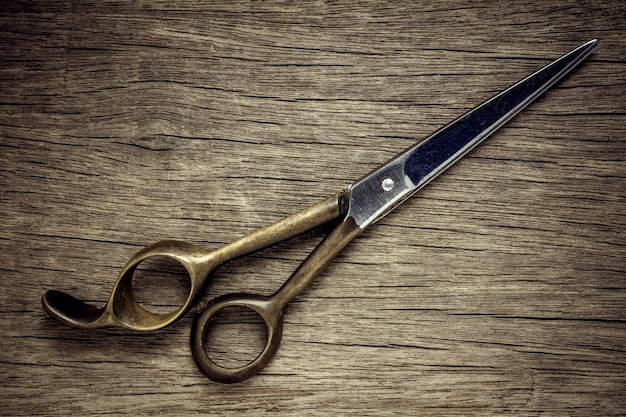 Old hairdressing scissors on wood background