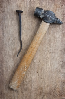 Old hammer and a rusty nail on a blackboard