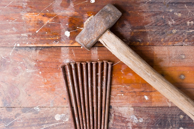 Old hammer with rusty nails and wooden background