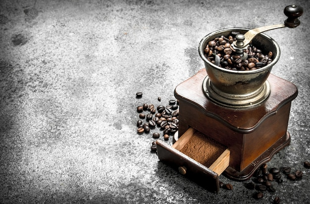 コーヒー豆と古いハンドグラインダー。素朴な背景に。