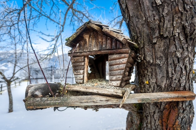 雪の降る冬の日の木に古い手作りの巣箱