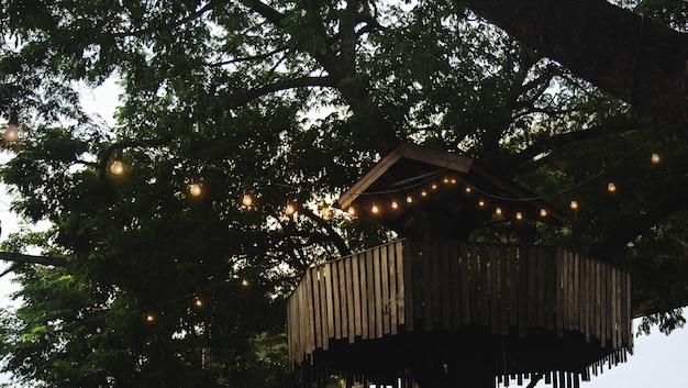 Старый деревянный домик на дереве с классической лампой для наружного