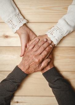 Старые руки пожилой пары вместе, взявшись за руки