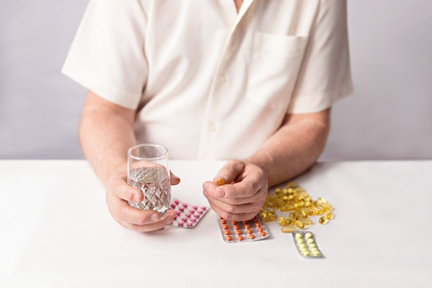 Old hands with pills and a glass of water, medicine on the table.