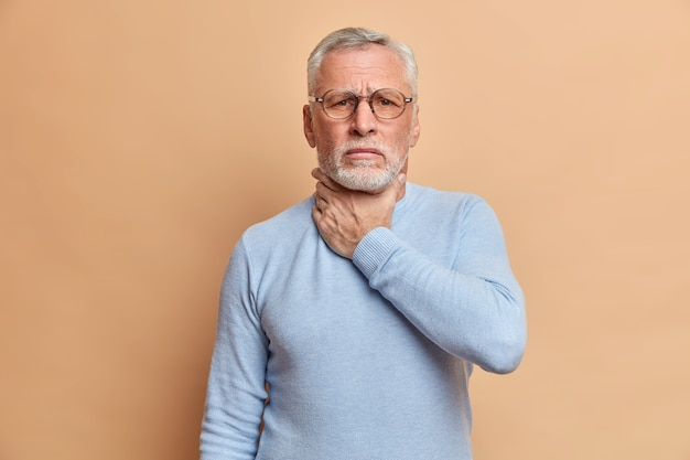Old handsome bearded man touches neck suffocates because of painful strangle feels pain in throat while swallow wears casual jumper isolated over beige studio wall
