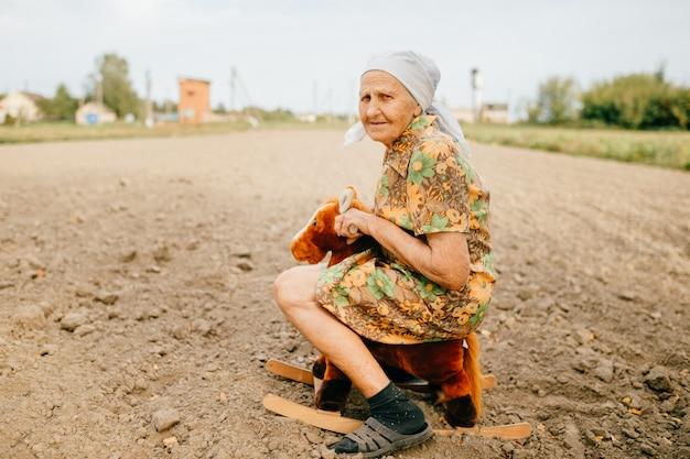 古い幸せな女の子供時代の思い出。フィールドでおもちゃの馬に乗って奇妙な奇妙な高齢女性。 great祖母のアウトドアカントリーライフスタイルの肖像画。