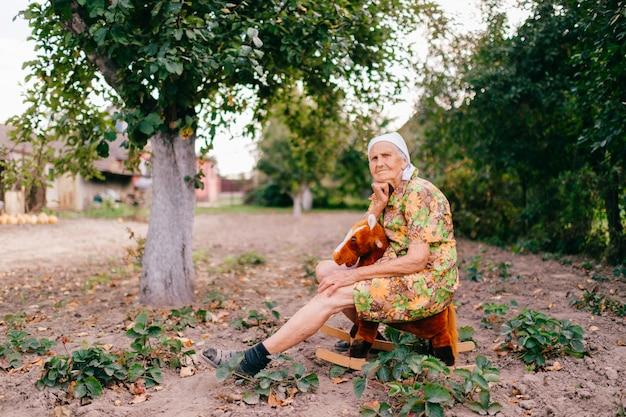古い幸せな女の子供時代の思い出。庭でおもちゃの馬に乗って奇妙な奇妙な高齢女性。 great祖母のアウトドアカントリーライフスタイルの肖像画。