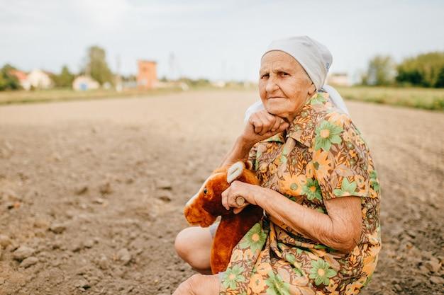 古い幸せな女の子供時代の思い出。奇妙な珍しい老婦人がフィールドでおもちゃの馬に乗って。 great祖母のアウトドアカントリーライフスタイルの肖像画。
