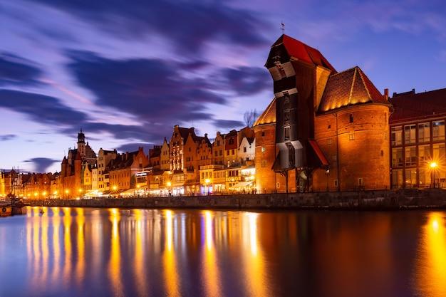 夜のグダニスクの旧市街にある旧港クレーンと市門ズラウ