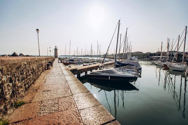 Old harbour full of boats in desenzano del garda. brescia, lombardy, italy. city centre of desenzano del garda. marina on lake garda.