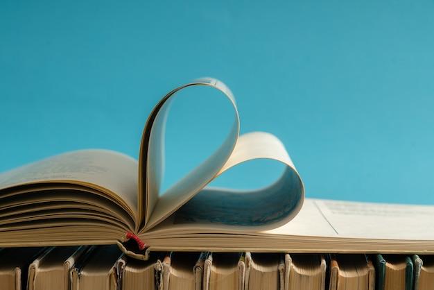 古いハードカバーの本のページは、バレンタインデーの愛のためにハートの形に飾ります。