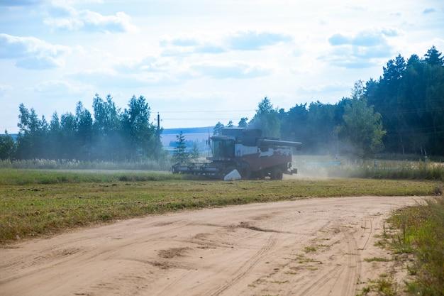 오래 된 수확기는 들판을 쟁기질합니다. 수확기는 뿌린 농업 분야 여름날에서 밀을 수확합니다