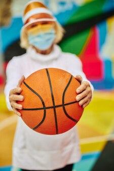 Старая, здоровая и жизнерадостная дама на красочной площади на открытом воздухе в маске и держит баскетбольный мяч