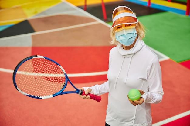 Старая, здоровая и жизнерадостная дама на красочной площади на открытом воздухе в маске и держит теннисную ракетку с мячом