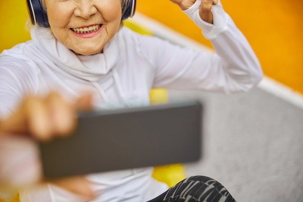 Old, healthy and cheerful lady on a colourful square outdoors wearing headphonesand holding smartphone