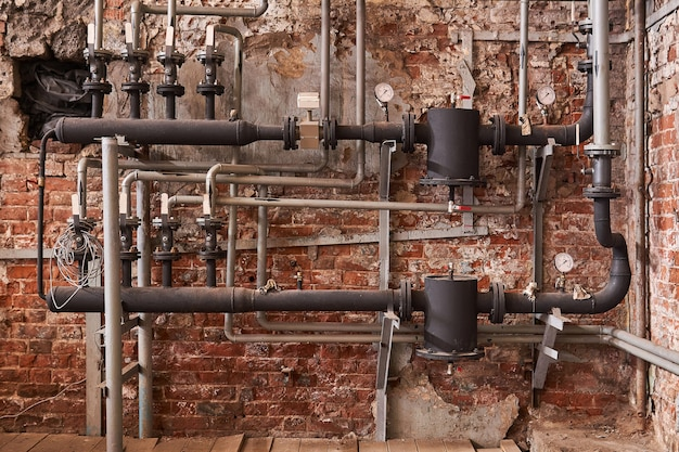 Old heating system of an industrial building with many pipes and pressure gauges