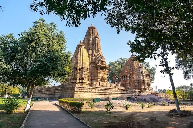 木々に囲まれたインドのカジュラホの西部にある、チャンデーララージプートによって建てられた古いヒンドゥー寺院。緑の草の上の青い空に対して、若くて古いベージュの構造のための白灰色。
