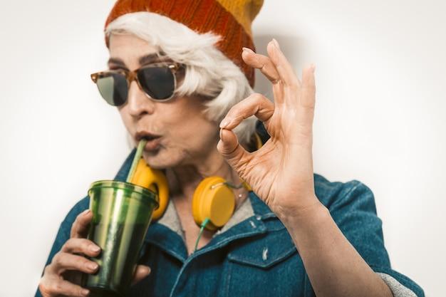 오래 된 hipster 여자 음주와 확인 제스처를 하 고