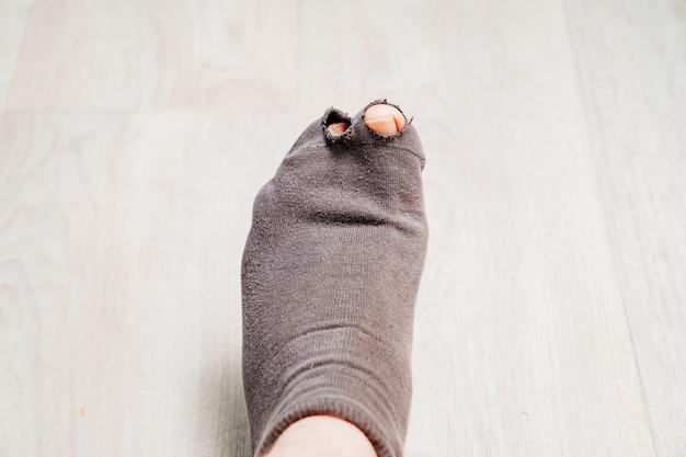 足に古い穴あき靴下。貧困。新しい服を買うお金の不足。