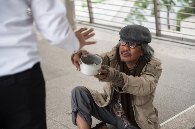 古いホームレスの男が都市でお金を求める