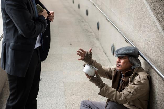 ホームレスの老人がお金を頼む