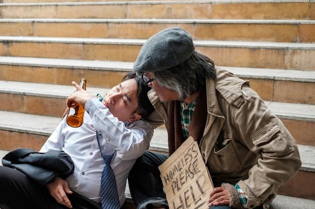 ホームレスの老人が酒瓶を持つビジネスマンの問題に耳を傾けている