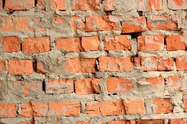 슬롯과 시멘트가 있는 오래된 수평 벽돌 벽