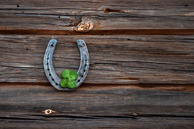 Old horseshoe and four leaf clover on a vintage wooden board.