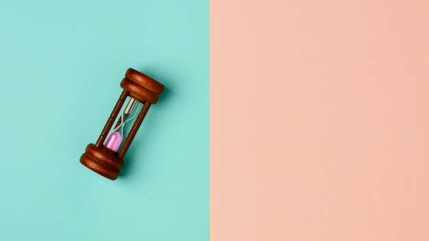 Old hourglass on blue and pink background