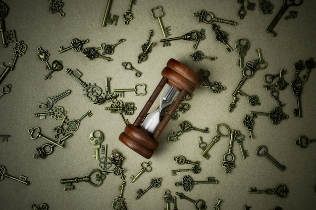 Old hourglass and classic keys on brown paper background